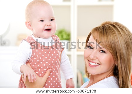 Closeup portrait of  happy mother with newborn baby - indoors