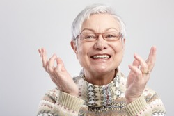 Closeup portrait of happy old woman gesturing by hands.