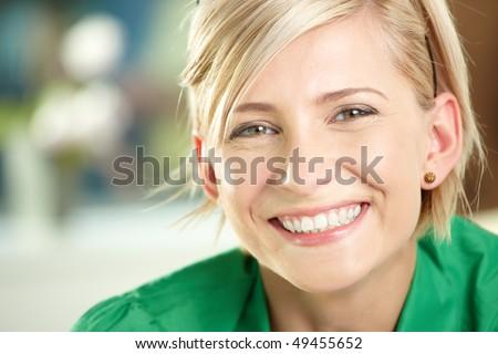 Closeup portrait of happy young businesswoman wearing green shirt, smiling.