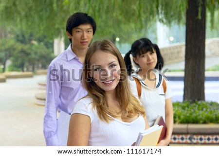 Closeup portrait of happy young girls and boy. Students outside school holding books. Group of people looking smiling together. American and Asian teenagers studying outside of university campus.