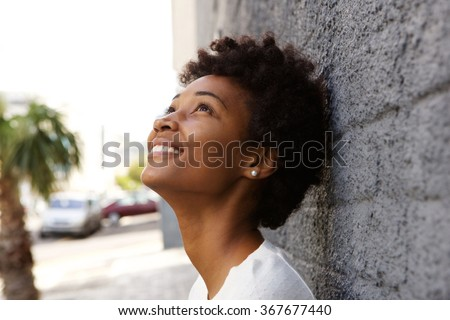 Closeup portrait of happy young woman leaning to a wall and looking up  #367677440