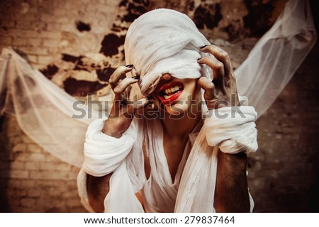 Closeup portrait of insane creature scratching her closed by bandage drawn face and red lips at bricks wall background.