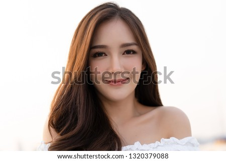 Closeup portrait of inspired caucasian Asian smilling and looking at camera on roof top.Concept woman lifestyle.