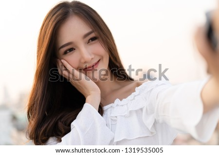 Closeup portrait of inspired caucasian Asian smilling and taking selfie on roof top.Concept woman lifestyle.