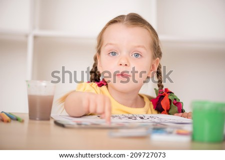 Closeup portrait of little beautiful kid, cute girl painting and pointing at her drawing with finger, pens and paints on the desk, interior shot