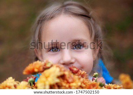 Closeup portrait of little girl with big beautiful eyes and with bouquet of wildflowers. Girl with bouquet of daisies. Kid with bouquet of summer flowers. Girl with bouquet of chrysanthemums. Allergy.