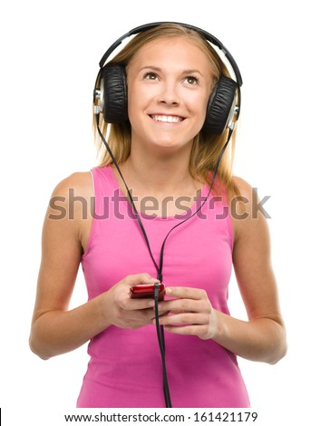 Closeup portrait of lovely teen girl enjoying music using headphones, isolated over white