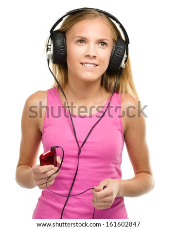 Closeup portrait of lovely teen girl enjoying music using headphones, isolated over white - stock photo