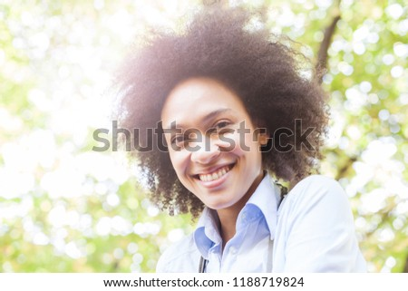 Closeup portrait of lovely young african american woman smiling in nature ,positive face expression, carefree outdoor lifestyle  #1188719824