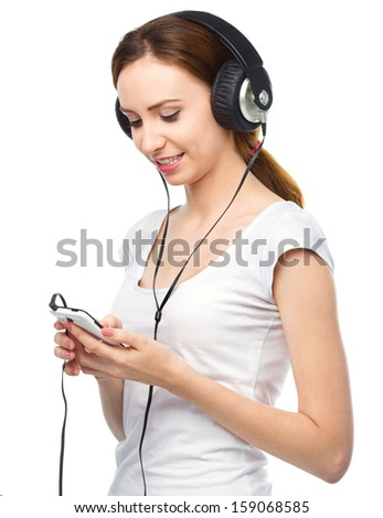 Closeup portrait of lovely young woman enjoying music using headphones, isolated over white