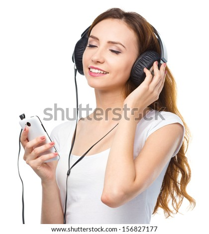 Closeup portrait of lovely young woman enjoying music using headphones while closed her eyes, isolated over white - stock photo