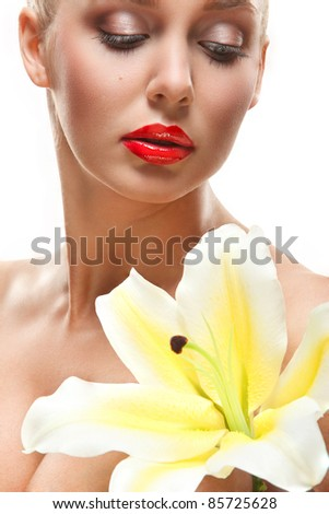 closeup portrait of lovely young woman with yellow lily over white background
