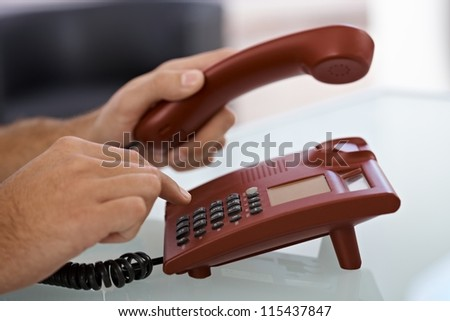 Closeup portrait of male hand dial on red landline phone.