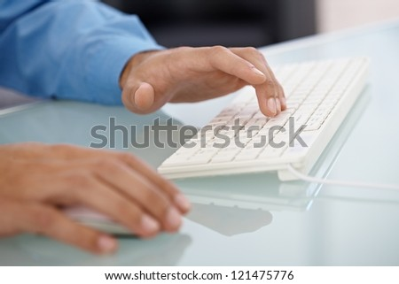 Closeup portrait of male hand typing on desktop computer keyboard, using mouse, selective focus. - stock photo