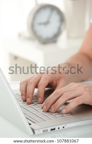 Closeup portrait of male hands typing on laptop computer keyboard.