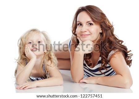 Closeup portrait of mother and daughter in white studio - stock photo