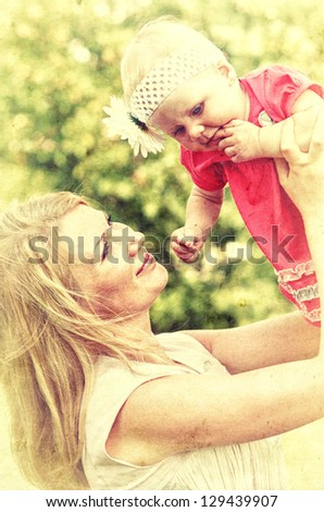 Closeup portrait of mother with her baby at outdoors. Vintage style photo.
