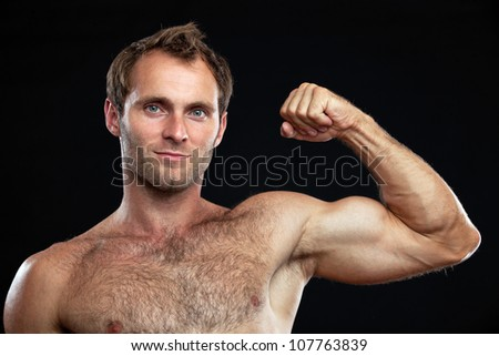 Closeup portrait of muscular man flexing his bicep against black background