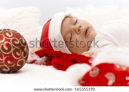 Closeup portrait of newborn baby sleeping in santa hat with christmas ornament.