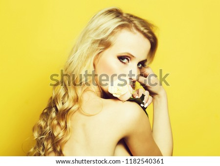 Closeup portrait of one beautiful sexy passionate blonde woman with long curly hair in studio with bare shoulder and brigt makeup holding rose flower near face on yellow backdrop, horizontal picture
