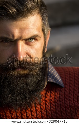 Closeup portrait of one handsome senior serious man with long black beard in red sweater looking forward sunny day outdoor on natural background, vertical picture