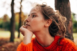 Closeup portrait of pensive womanlooking away, wearing orange knitted sweater posing on fall nature background. Beautiful female has thoughtful expression, resting outdoor in the park.