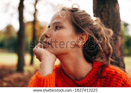 Closeup portrait of pensive womanlooking away, wearing orange knitted sweater posing on fall nature background. Beautiful female has thoughtful expression, resting outdoor in the park. Foto d'archivio ©