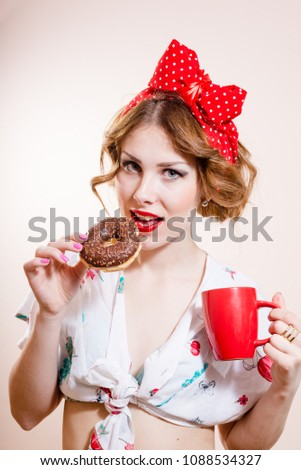 closeup portrait of pinup girl beautiful blond young woman with excellent dental care teeth having fun eating donut and drinking coffee looking at camera on white background - Shutterstock ID 1088534327