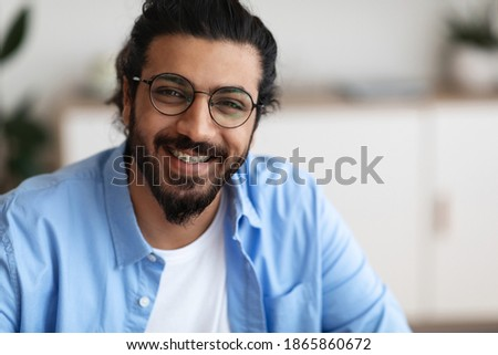Closeup Portrait Of Positive Indian Guy With Dental Braces And Eyeglasses Smiling At Camera, Handsome Bearded Millennial Man With Brackets On Teeth Posing Indoors, Selective Focus With Copy Space ストックフォト ©