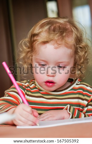 Closeup portrait of preschooler with strawberry blonde curly hairs who draws in the sketchbook by pencil and looks down