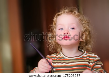 Closeup portrait of preschooler with strawberry blonde curly hairs who draws in the sketchbook by pencil and looks into the lens
