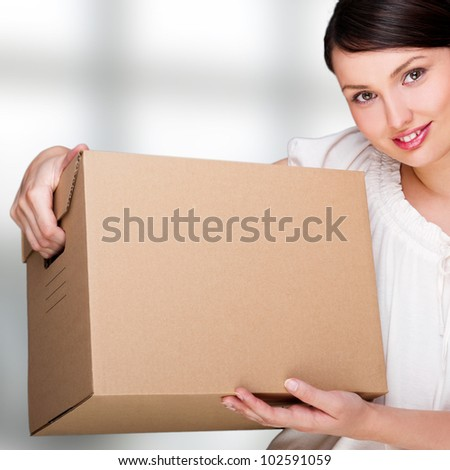 Closeup portrait of pretty adult woman holding a box at office building. New staff member concept