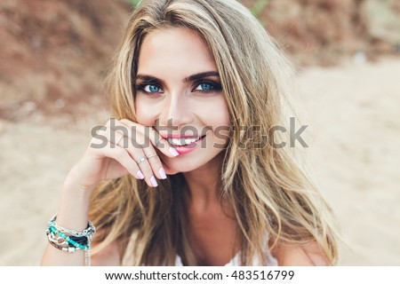 Stock Photo Closeup portrait of pretty blonde girl with long hair and blue eyes posing on rocky beach. She is smiling to the camera.