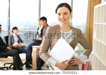 Closeup portrait of pretty cheerful business woman in an office environment holding laptop. Large panoramic window on background