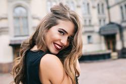 Closeup portrait of pretty girl with long curly hair smiling to camera in city on old building background. She wears black dress, red lips. View from back.