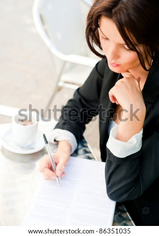 Closeup portrait of pretty woman sitting at cafe and signing documents while drinking her coffee. Natural light Outdoors