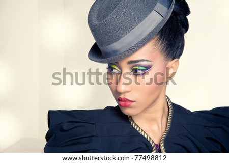 Closeup portrait of pretty young showgirl wearing a hat, with stage lights on background