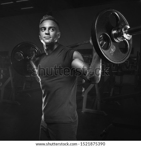 Closeup portrait of professional bodybuilder workout with barbell at gym. Black and white photo. Muscular man training squats with barbells over head