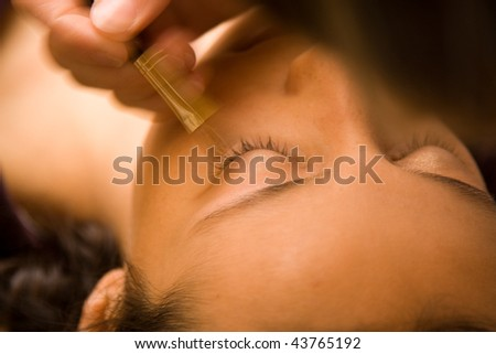 Closeup portrait of reclining young woman seen from top of head using makeup brush.