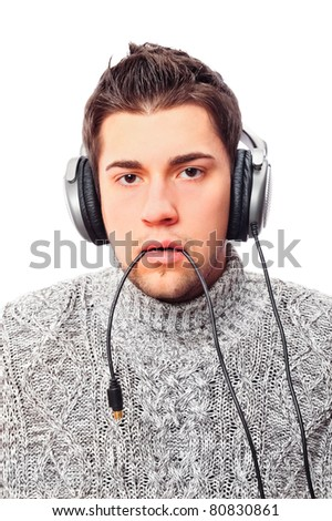 Closeup portrait of sad young man wearing domestic sweater holding cable of headphones in his mouth and looking at camera