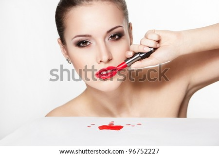 closeup portrait of sexy caucasian young woman model with glamour red lips,bright makeup, eye arrow makeup, purity complexion with red lipstick. Perfect clean skin. blood on table