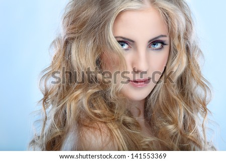 Stock Photo Closeup portrait of sexy whiteheaded young woman with beautiful blue eyes on blue  background
