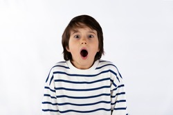 Closeup portrait of shocked scary  surprised young boy of nine years old, eyes and mouth wide open,  shouting, isolated on white background. Strong emotion facial expression feeling.