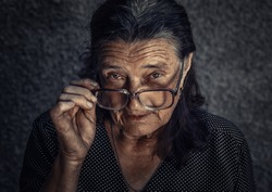 Closeup portrait of skeptical old woman looking suspicious, some disgust  disapproval on face isolated dark grey background. Negative human emotions, facial expressions, feelings. Dramatic toned photo