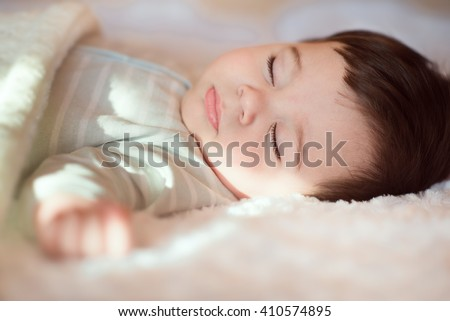 Stock Photo Closeup portrait of sleeping baby covered with knitted blanket