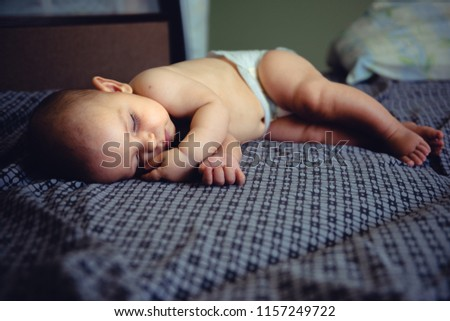 Closeup portrait of sleeping on the grey bed in diaper innocence concept #1157249722
