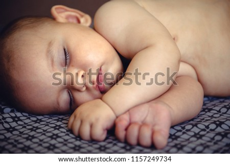 Closeup portrait of sleeping on the grey bed in diaper innocence concept #1157249734