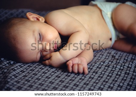 Closeup portrait of sleeping on the grey bed in diaper innocence concept #1157249743