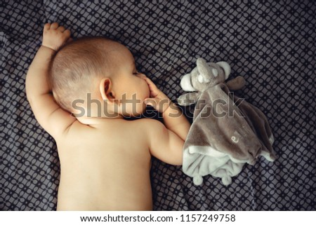 Closeup portrait of sleeping on the grey bed in diaper innocence concept #1157249758