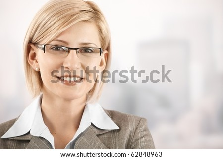Closeup portrait of smiling blonde businesswoman wearing glasses.?